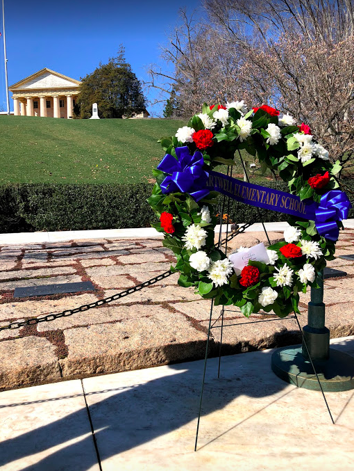 Wreath laying at gravesite of John F. Kennedy with Arlington House in the background.